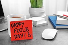 Note with phrase. `Happy Fool`s day` on office table. 1st April celebration Royalty Free Stock Photos