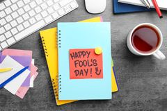 Note with phrase. `Happy Fool`s day` on office table. 1st April celebration Stock Photography
