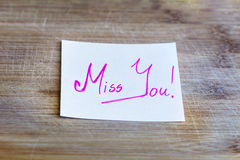 Note with pink miss you sign  on a wooden background Stock Images