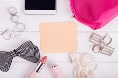 Note with place for text, female trivia. Accessories, lipstick, phone, cosmetic bag. A gift for women`s day Stock Photo