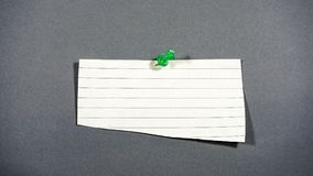 Note with a push pin. A note sheet with a green push pin on a dark grey background stock image