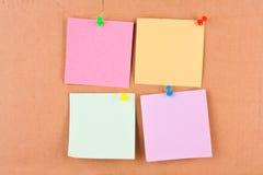 Note quatre en blanc avec les broches colorées Photos libres de droits