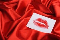 Note on red silk. A print of lips Stock Photo
