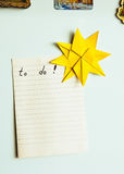 Note on refrigerator. To do note on a refrigerator decorated with an origami sun Royalty Free Stock Photos