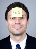 Note says YES. Business man wear a note that says YES Royalty Free Stock Image