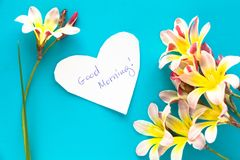 Note in shape of heart with words Good Morning. Note in shape of heart with words Good Morning, with flowers on blue surface Royalty Free Stock Photo