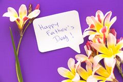 Note in shape of heart with words . Note in shape of heart with words `Happy Father`s Day!` with flowers on purple surface Royalty Free Stock Image