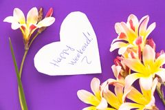 Note in shape of heart with words. Note in shape of heart with words `Happy Weekend!` with flowers on purple surface Stock Photos