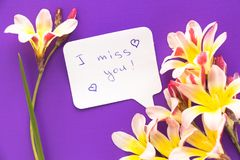 Note in shape of heart with words . Note in shape of heart with words `I miss you!` with flowers on purple surface Royalty Free Stock Images