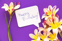 Note in shape of heart with words . Note in shape of heart with words `Happy Birthday!` with flowers on purple surface Royalty Free Stock Image