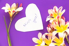 Note in shape of heart with words . Note in shape of heart with words `Miss you!` with flowers on purple surface Royalty Free Stock Images