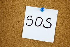 Note with SOS inscription. Sticky note with SOS inscription pinned on a cork bulletin board. Businnes concept royalty free stock images