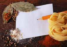 Note,spices and pasta on a wood cutting board Royalty Free Stock Images