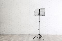 Note stand with music sheets near brick wall. Space for text. Note stand with music sheets near brick wall indoors. Space for text stock image