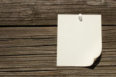 Note Tacked Onto Wood Background. White note tacked onto a wood wall Stock Image