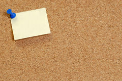 Note tacked to cork board. Cork board with blank note attached with thumb pin Royalty Free Stock Photo