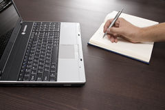Note taking and laptop. A view of a person's hand writing in a notebook on a brown table with a laptop computer nearby Royalty Free Stock Photo