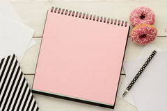 Open notebook and donuts. Open notebook , skechbook or scrapbook with pink blank page, pen and donuts on white wooden desk. Ideas, notes or plan writing concept royalty free stock photo