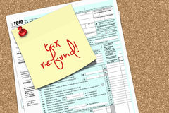 Note with tax refund text and 1040 form pinned to pin board Stock Photo