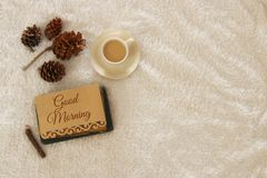 Note with text: GOOD MORNING and cup of cappuccino over cozy and warm fur carpet. Top view. Royalty Free Stock Images
