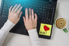 A note of text 14.02 written on a paper sticker. Background computer, laptop, woman`s hands on the keyboard. Stock Photo