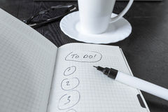 Note to do close-up. Note to do, cup, glasses and pen on black table Royalty Free Stock Images