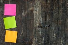 Note variopinte del bastone sulla tavola di legno Fotografie Stock