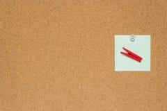 Note variopinte una con gli a pressione bianchi e mollette da bucato isolate su un fondo del sughero fotografie stock