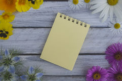A note on a wooden surface framed by summer flowers 1 Royalty Free Stock Photos