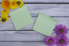 A note on a wooden surface framed by summer flowers 7 Stock Photo