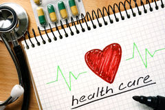 Note with words HEALTH CARE concept. Stock Photography