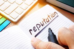 Note with written word reputation. Note with written word reputation on a desk royalty free stock image