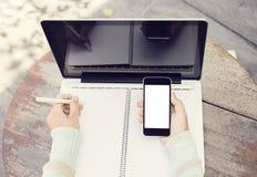 Notebbok, computer portatile in bianco e telefono cellulare all'aperto Fotografia Stock