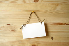 Noteboard on wooden wall. White paper nameboard for notes hanging with rope on wooden background Royalty Free Stock Photos