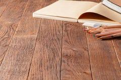 Noteboks und bunte Bleistifte auf dem Holztisch, Radiergummi Stockfotos