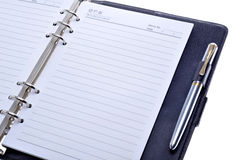 Notebook. A blank notebook and a pen on a white background Royalty Free Stock Photos