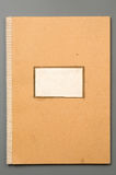 Notebook. Yellow cardboard notebook cover isolated over grey Royalty Free Stock Photography