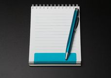 Notebook. Clean notebook and the pen on a black textural surface Royalty Free Stock Photo