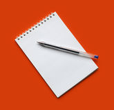 Notebook. And pen on the orange background Stock Image
