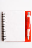 Notebook. Red notebook and ball point pen over white background Royalty Free Stock Images