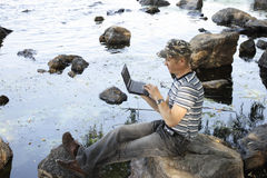 Notebook. Man works at notebook sitting on stone Stock Images
