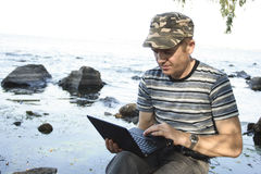 Notebook. Man works at notebook sitting on stone Royalty Free Stock Photo