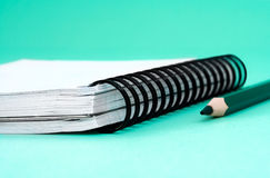 Notebook. With a pointed pencil, green background Royalty Free Stock Images