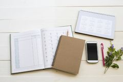 Notebook account planner ,calendar and mobile phone for business work. Arrangement flat lay style on background white at office royalty free stock photo