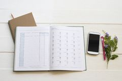 Notebook account planner  and mobile phone for business work. Arrangement flat lay style on background white at office royalty free stock photo