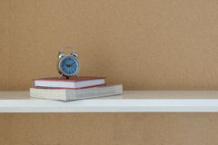 Notebook and alarm clock on shelf for decoration room. Stock Images