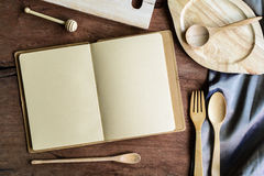 Notebook amd wooden utensil in kitchen on old wooden background Royalty Free Stock Images
