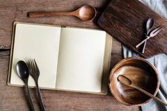 Notebook amd wooden utensil in kitchen on old wooden background Royalty Free Stock Photos