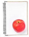 Notebook and apple isolated Royalty Free Stock Images
