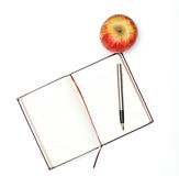 Notebook and apple Stock Images
